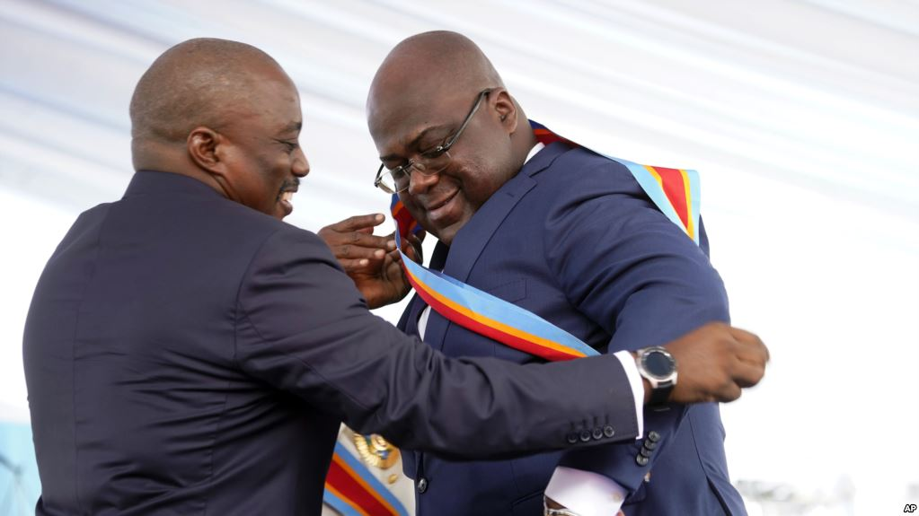 Congolese President Felix Tshisekedi, right, receives the presidential sash from outgoing president Joseph Kabila (photo credit: AP)