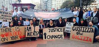Demonstrators hold a 'No Change No Justice' Banner (photo credit: @TinaUrso1/Twitter)