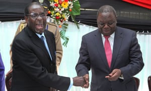 Robert Mugabe shakes hands with Morgan Tsvangirai after signing the new constitution into law (photo credit: Tsvangirayi Mukwazhi/AP)