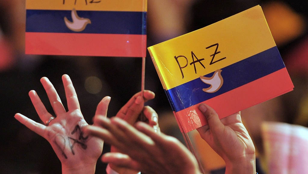 Supporters of the peace (Paz) process hold the Colombian flag (photo credit: Warscapes)