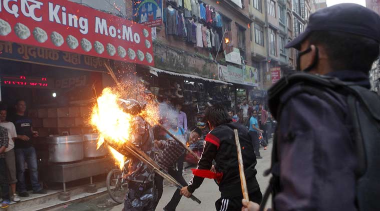 Nepalese protesters hit a policeman with a torch during a rally in Kathmandu, Nepal, Saturday, August 15, 2015 [photo credit: AP]