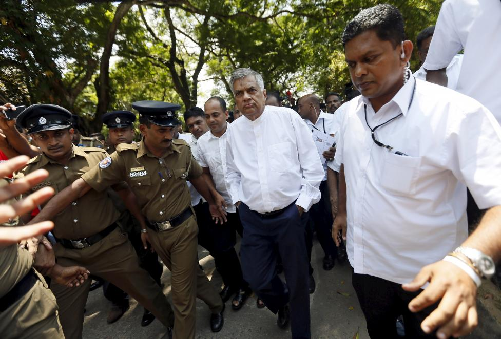 Sri Lanka's Prime Minister Ranil Wickremesinghe (C) arrives at a polling station during a general election in Colombo, August 17, 2015 [photo credit: Reuters]