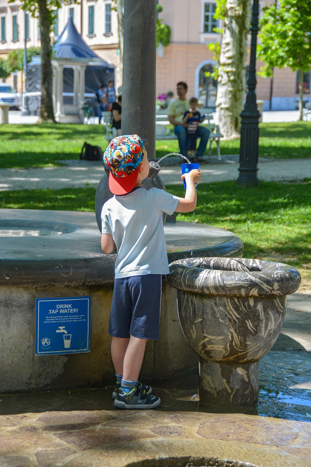 A boy drinks water from a public water tap in Ljubljana (Photo credit: The visit Ljubljana website)